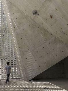 Twenty-thousand pieces of aluminium form a chain-mail blanket over this concrete performance venue