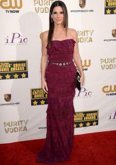 Sandra Bullock con un vestido palabra de honor de volantes en color frambuesa con cinturón joya, de Lanvin.