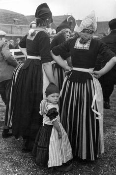 Nederlandse vrouwen en kind in traditionele kleding bij een voetbalwedstrijd - fotograaf:  Alfred Eisenstaedt. Volendam, Nederland, 1932.