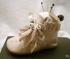 baby shoe pincushion embellished with broken pieces of vintage earrings