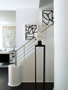 In the Mimran maisonette, the wall along the staircase features art by Al Held. The custom railing is made of polished nickel. Photo by Simon Upton | Design John Barman