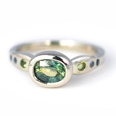Modern alternative custom engagement ring in palladium with sustainably sourced aqua sapphire and blue sapphire and peridot detail stones. Custom wedding rings by Abby Sparks Jewelry, custom jewelry designer in Denver, Colorado.