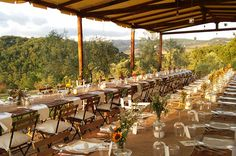 Country wedding reception with burlap for the table runners and rustic wedding decor with mason jars centerpieces filled of wildflowers, sunflowers and candles