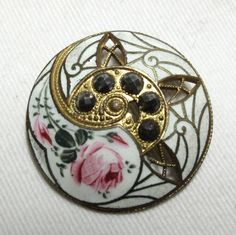 "pierced antique gilt brass Champleve enamel button with cut steel   Beautiful antique French champleve enamel button with hand painted pink rose. Interesting and unusual piercings in gilt brass and cut faceted steel in the center. This is a gorgeous antique 18th century sewing button.   Excellent condition   Measures 1 -1/4""  SOLD $49.99"