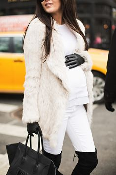 Neutral fur coat over a white maternity top, white leggings, black boots and an oversize bag! Winter maternity style!