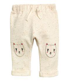 BABY EXCLUSIVE/CONSCIOUS. Sweathose aus Bio-Baumwolle mit buntem Tweedeffekt. Die Hose hat Stickapplikationen auf den Knien und einen elastischen Bund mit Zierkordelzug. Fixierter Beinumschlag.