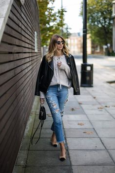 Emma Hill wears lace up sweater, black leather biker jacket, ripped raw hem jeans, ring handle zara bag, toe cap camel shoes, chic autumn fall outfit