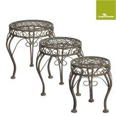 Een set ijzeren bijzettafels met sierlijke elementen.Deze tafeltjes worden binnen of buiten in de tuin gebruikt.