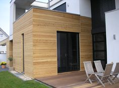 Geschlossene Rhombusschalung aus sib. Lärchenholz kombiniert mit Sichtbeton und Putz. Das Deckensektionaltor wurde ebenfalls mit Holz verkleidet.