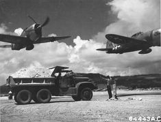 P-47D Thunderbolt Big Squaw and another P-47 of the 19th Fighter Squadron make a low level pass over East Field Saipan October 1944. Note IH M-5 Truck and T/5 James B Lazar from the 805th Aviation Engineer Battalion.