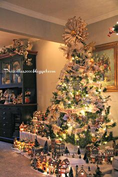 Part of the Christmas  village extends into the dining room ..It is wrapped around this tree in the living room