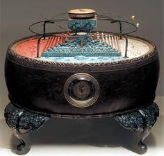 須弥山の須弥とは梵字「Sumeru」(スメール)の音写で妙高と訳される。古代インドの宇宙観で、一須弥世界の中心にある高山を指す。仏教ではこの須弥山説を踏襲しており、江戸末期にはこれを一般に易しく理解させるため、リンが鳴り太陽と月が時計仕掛けで動く模型を考案した。これが「須弥山儀」である。    (Toyama:)  須弥山儀とは   須弥山儀は上記の須弥山を中心とした宇宙観を説明するために、実際に太陽、月、星がどのように動くかを実際に動かして見せるための器具です。重錘式の時計の機構を利用して、1年間の太陽の動き、1月の月の動き、1日の太陽、月、星の動きを再現します。須弥山儀の胴体の部分には時計も組み込まれています。     この須弥山儀は天台宗仏教の天文学を修めた円通(1754~1834)の主張に基づき、弟子の環中、晃厳らが縮象儀とともに考案したもので、田中久重などが製作しています。