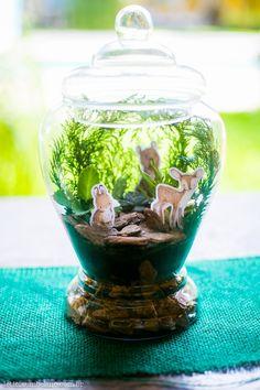 Centro de mesa para chá de bebê com tema Woodland. Feito em aquario de vidro com cascalhos de maderia e figuras de bichinhos em papel. Foto: Leticia Umbelino