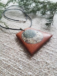 Unique gift for women. Made of bilinga wood with a crushed shell, herbal inlay and finished with varnished oil mixture, this pendant has very nice natural patterns. The glossy finish is quite pleasant to touch and provides high protection against moisture and dirt. The necklace cord is