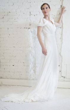 Off-white silk-chiffon gown with raw-edged lace trims. Alberta Ferretti gown has gathered pleats at bodice, draped cap sleeves, a draped sash from back of one shoulder, a press-stud fastening sash at