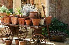 .I like this idea... love the old wagon.. and all of the terra cotta pots... nice!