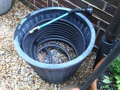 garden hose stored in a large planter - much more attractive than those hose holder thingies