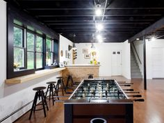 A bold, dark ceiling contrasts with the bright white walls in this inviting basement. The large, brightly lit space leaves plenty of room for play at the foosball table, as seen on HGTV's Cousins Undercover.