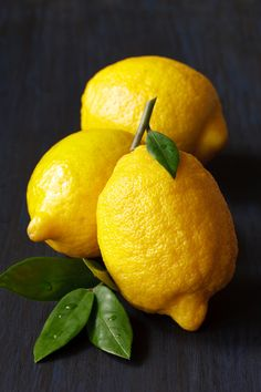 https://flic.kr/p/d73qb7 | Lemon. | Beautiful fresh lemons with leaves on a dark blue board.