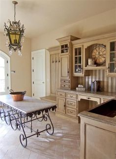 Use of classic style French marble top pastry table with iron base as a kitchen island
