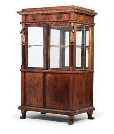 Unusual Biedermeier Vitrine,  Circa 1820/25. Made in softwood with mahogany veneer, stepped angles with partly ebonised caryatids, finely carved and gold-painted mouldings, two bombé doors, two glazed doors, interior compartments and carved paw feet. 164 x 101.5 x 66.5 cm.,