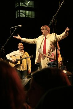 Garrison Keillor marvels at a little girl's amazing bird calls at the Prairie Home Companion Street Dance in St Paul, MN