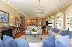 Light floods the living room through a wall of arched French doors that open onto the pool.