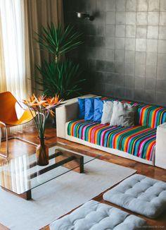 O ladrilho hidráulico preto instalado na parede da sala de estar garantiu um ar moderno ao ambiente.
