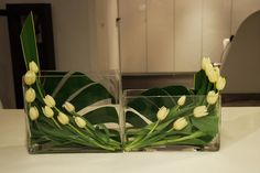 Simple arrangement with first tulips from Holland. Monstera´s & Phornium leaves, with the tulip flowers in ascending form, rectangular vases in two different sizes for make continuity to the arrangements. Less it is more.