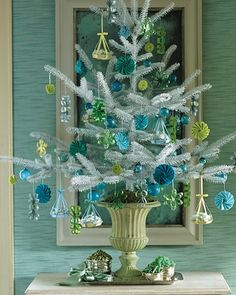 An assortment of colorful candy holders and basket ornaments creates a striking effect against a white tree.