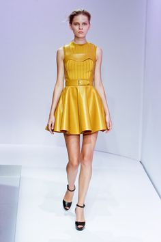 A girly dress stands out in bright yellow paired with patent black sandals.