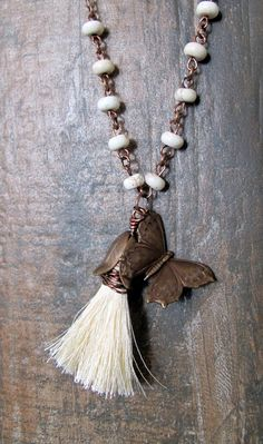 #ThePaintedCabeza ~ This beautiful necklace is made up of a cream colored silk tassel, wire wrapped, and hanging with a gorgeously detailed brass butterfly charm.