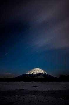 全面凍結した精進湖と小さな笠雲を被った富士山と流れる星と迫る雲(Fuji)