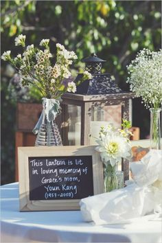 Memory tables are very popular at funeral....but what about at a wedding for relatives that cant be there? What a great and affordable idea to use chalk boards to describe what is on the table. In this case they wrote that the lantern was lit in loving memory of the departed. #funeral ideas, #celebration of life ideas, #memory table,