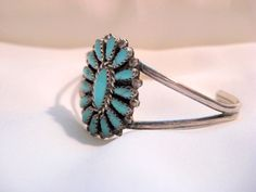 This is a handmade sterling silver and genuine turquoise petit point style Hopi bracelet signed HB. The artist mark is unidentified and therefore