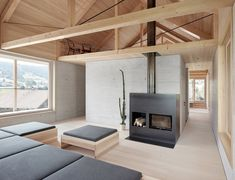 A small seating area is tucked into a loft-like space. Tagged: Living Room, Sofa, Wood Burning Fireplace, Ottomans, and Light Hardwood Floor. Photo 7 of 14 in A Minimalist Home Is Built Into Steep Terrain in an Austrian Valley