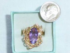 Dies ist ein wunderbares Anwesen cocktail Ring. Der Ring verfügt über einem großen ovalen Amethyst und echte Diamanten, montiert auf eine 14 k benutzerdefinierte gelb gold Einstellung. Es ist einem außergewöhnlichen Rahmen, wie es höher an den Finger, erstreckt sich die Finger verlängert. Die Einstellung hat ein swirly Design, Blätter mit Akzentuierung von einem Ende des Rings. Schön!  Die Amethyst misst ca. 14mm (etwas größer als 1/2) von 7mm groß. Der Runde echte Diamant ist etwa 2,5 mm…