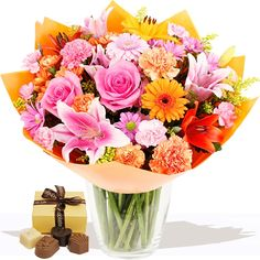 Pink & Orange Bouquet with Free Luxury Chocolates   A vibrant and exciting hand-tied of contrasting pale and deep pink with zesty, flame orange flowers. Carefully selected pink Oriental Lilies, large headed Roses with Germini daisies, handcrafted with a range of florist select varities in the hand. This is as a stylish hand-tied bouquet.