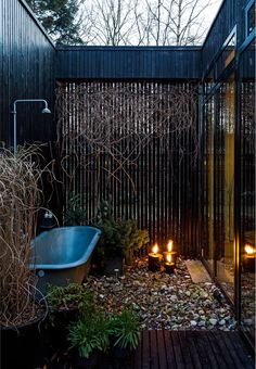 Rustic outdoor shower and bathtub on the terrace. To give a wellness feeling plants and candles are placed around it.