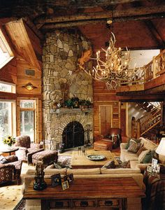 This is a cottage style room with high ceilings and  wood material implemented in its interior. The neutral tones in the room make the overall room feel cozy and inviting. The focal point is the fireplace in the decorative stone wall.