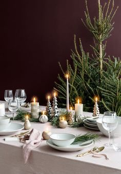 Delicate Christmas table setting with bright tableware, golden cutlery and green elements from nature.