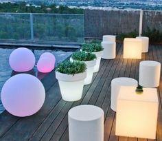 terrasse en bois décorée avec des pots de fleurs lumineux