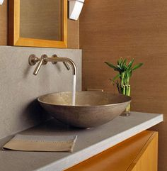 Love the vessel sink and that the faucets aren't on the counter. This has a very organic feel.