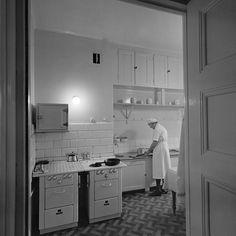 Köksinteriör. En kvinna rensar fisk - Stockholmskällan
