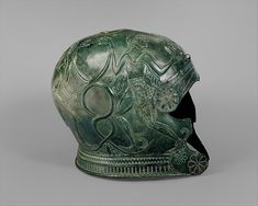 Bronze helmet, late 7th century B.C. Period: Archaic. Greek, Cretan. H. 8 1/4 in. (20.96 cm). Bronze helmet with two winged youths on each side who flank and grasp a pair of entwined serpents. I Metropolitan Museum