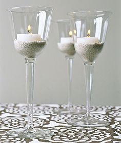 wine glasses filled with sand and tea light candle