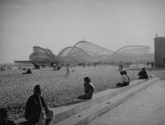 Long Beach, CA (ca. - People enjoy a day at the beach either in the water, strolling on the sand, sitting under umbrellas or visiting The Pike in this Long Beach scene. The Cyclone Racer roller coaster is in the background. Long Beach Pike, Long Beach California, California History, Southern California, Selma California, Vintage California, California Coast, Emotional Pictures, Beach Scenes