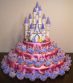 Massive princess castle cake display, but is really a modest size cake, an affordable Wilton castle kit, and lots of cupcakes.