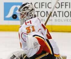 Calgary Flames goalie Karri Ramo, of Finland, has the puck whiz past his mask on a shot from a Colorado Avalanche player during the third period of an NHL hockey game Saturday, March 14, 2015, in Denver. The Avalanche won 3-2. (AP Photo/David Zalubowski)