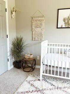 Boho neutral cactus desert theme nursery decor. Real deer head. Jenny Lind crib. Woven wall hanging. Dragon tree. Bentwood stool.